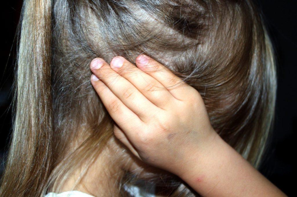 Foto di bambina preoccupata che si tappa le orecchie